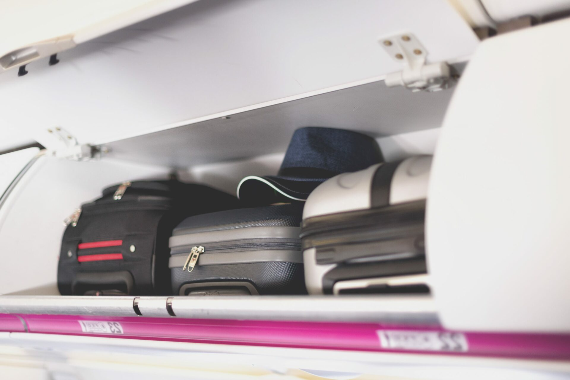 Hand-luggage compartment with suitcases in airplane. Carry-on luggage on top shelf of plane. Travel concept with copy space